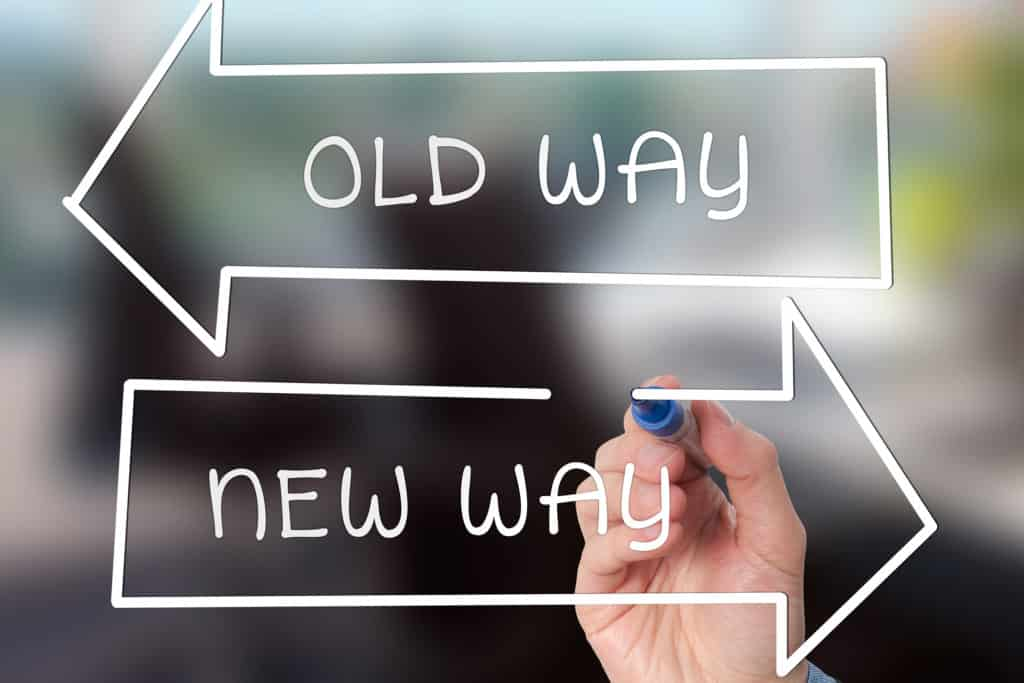 A hand holds a marker and is drawing an arrow to the left that says old way and one pointing to the right that says new way