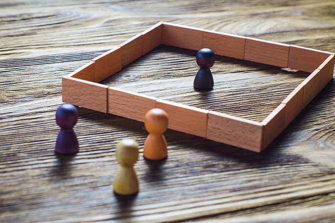 A wooden figure representing a person is inside a box while 3 others are outside the box