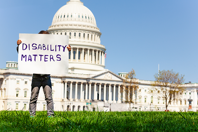 A person stands in front of a capital building holding a sign that says disability matters