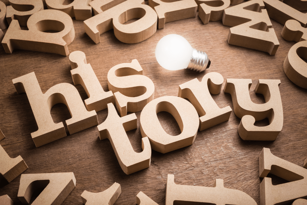 The word 'history' is spelled out in wooden letters with a lightbulb nearby