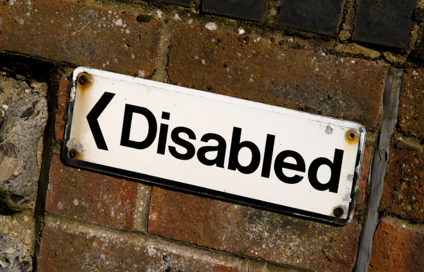 """A brick wall has a sign that points to the left and says """"disabled"""""""