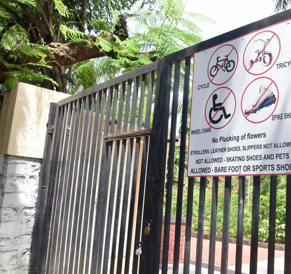 A metal gate has a sign with symbols that indicate no bicycles, no tricycles, no spiked shoes, no wheelchairs, no plucking of flowers