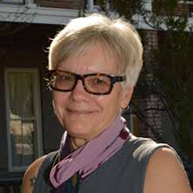 Woman with short white hair and glasses smiling